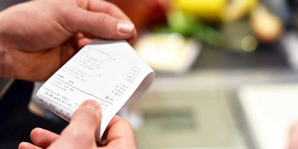 Hände mit Kassenzettel an der Kasse im Supermarkt // hands with receipt at the checkout in the supermarket